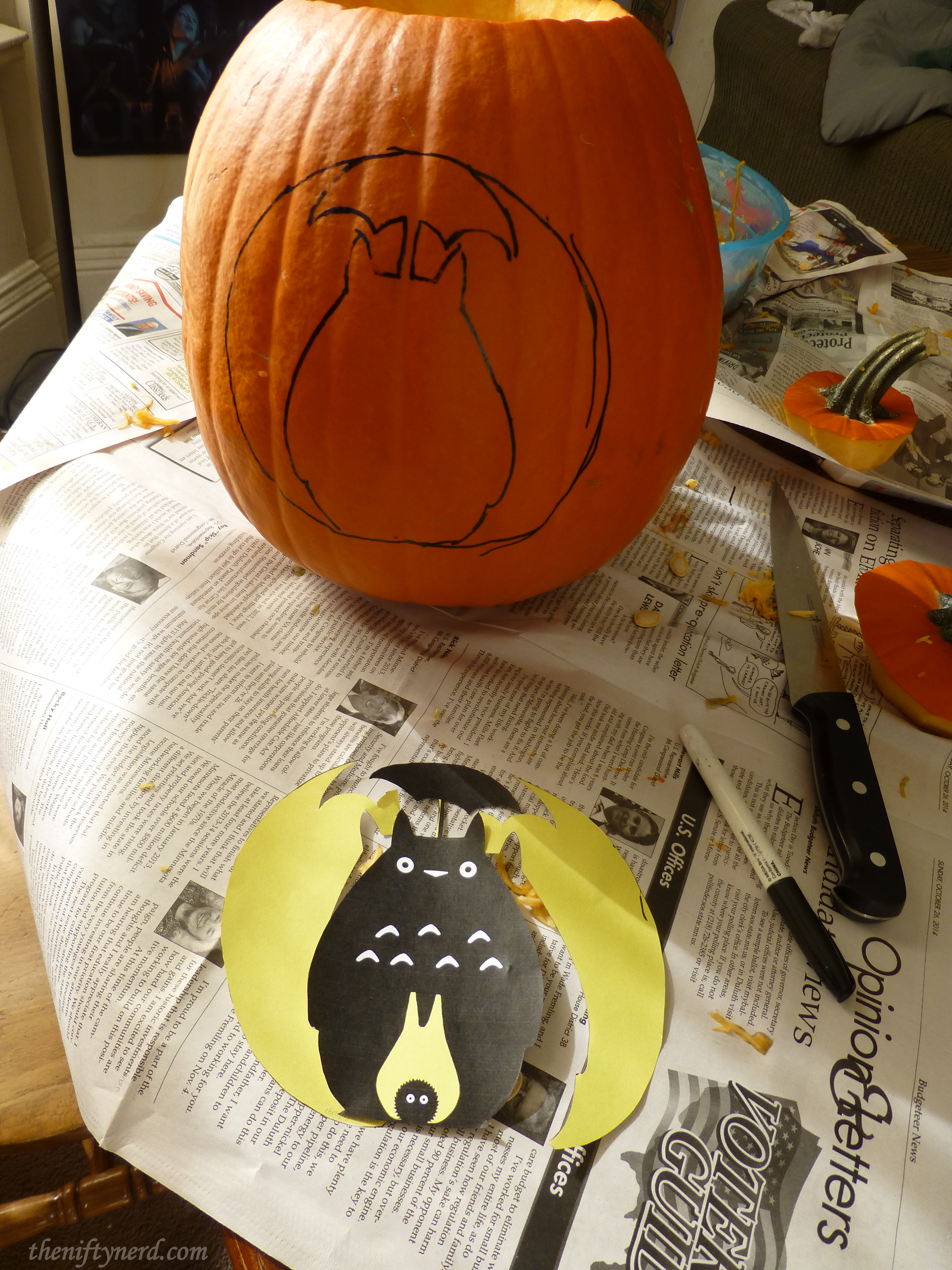 tracing totoro pattern into a pumpkin for cutting