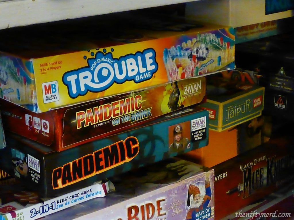 Closet shelf full of board games like Trouble and Pandemic