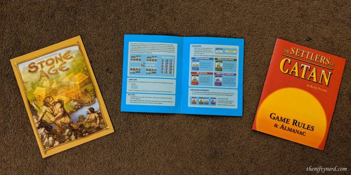 Rule books for Stone Age, Machi Koro, and Settlers of Catan