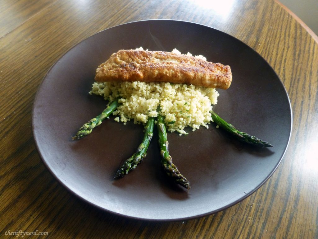 fried fish over a bed of couscous and grilled asparagus