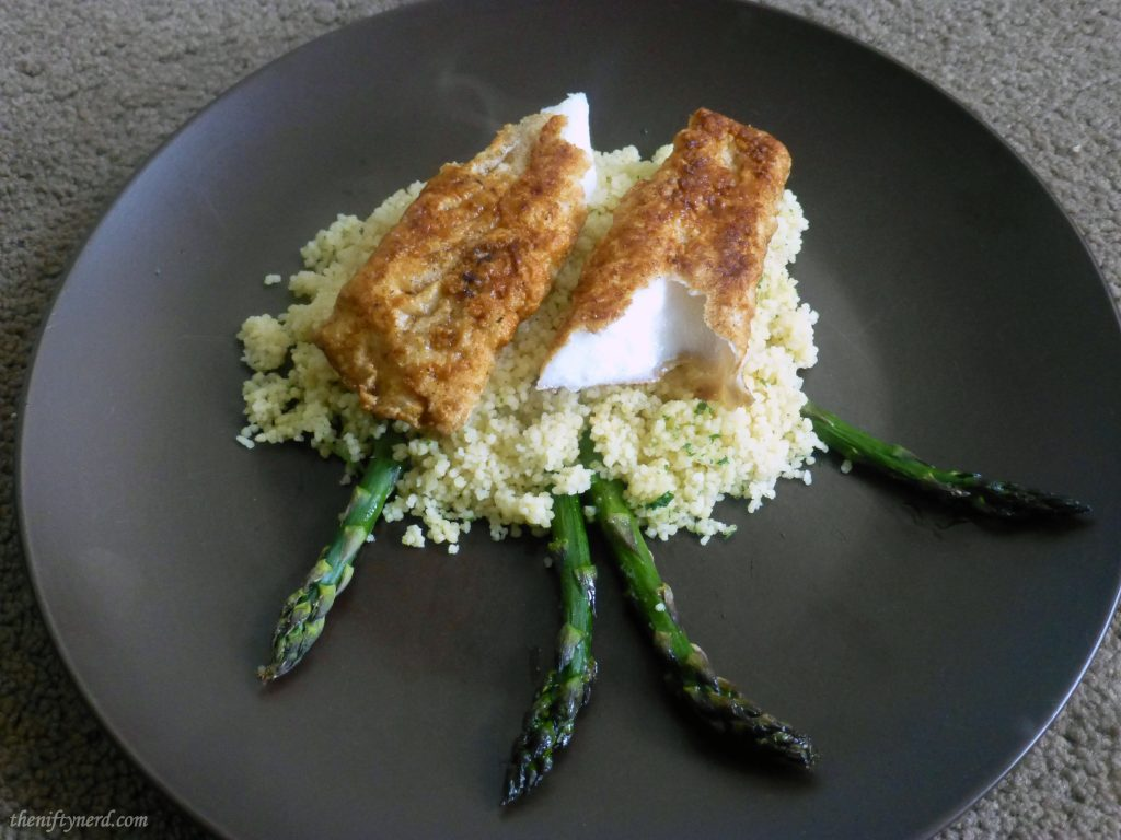 fried halibut over a bed of cous cous and grilled asparagus
