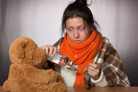 sick girl with a teddy bear and medicine